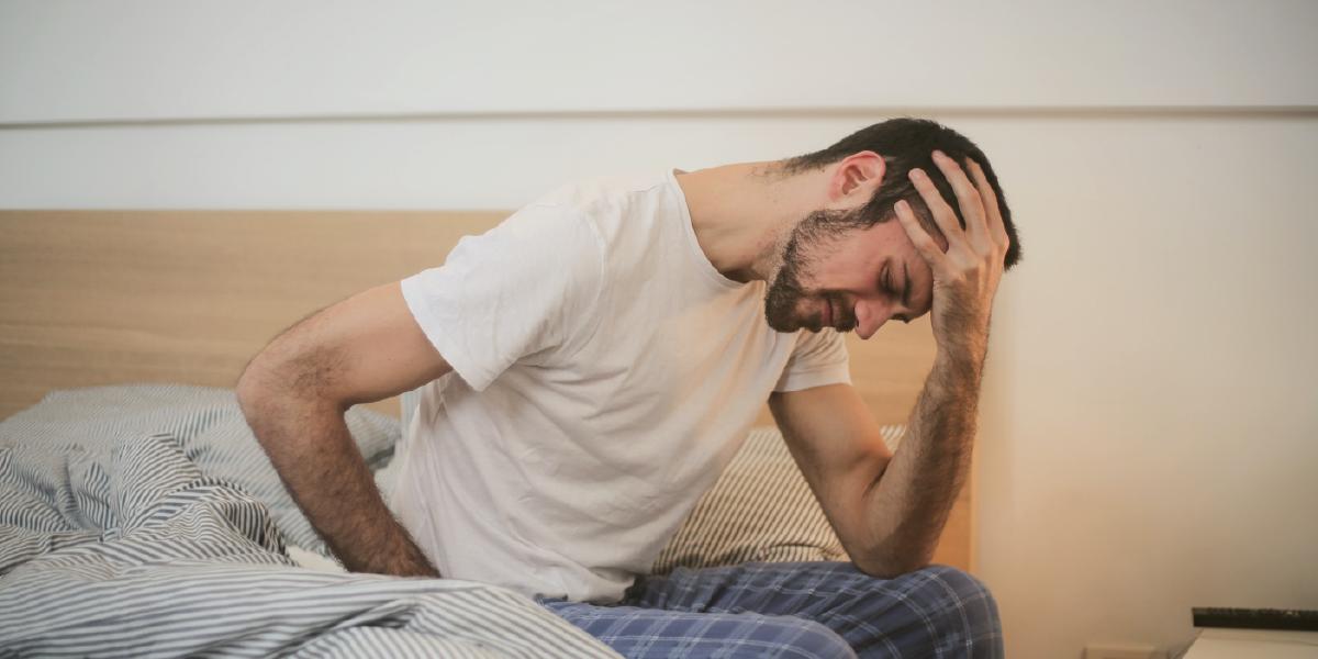 homem jovem sentado na cama , com a mão na cabeça, aparentando sentir dor