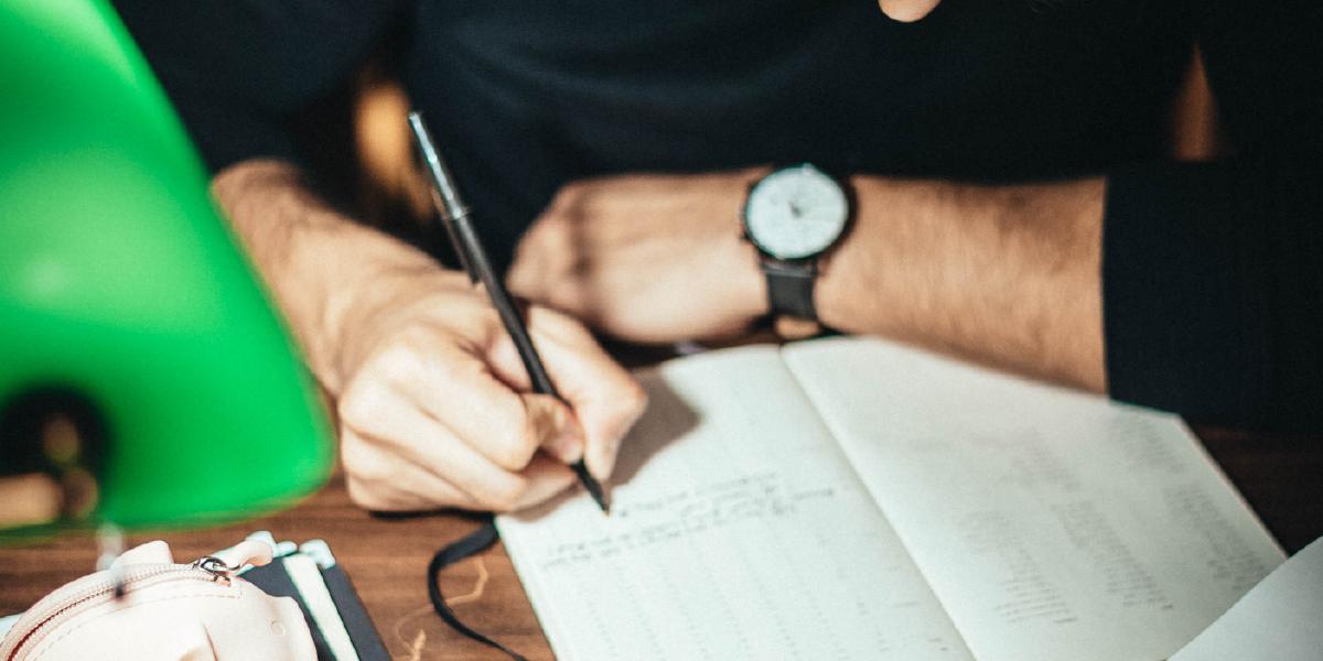 homem fazendo anotações em caderno