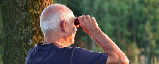 homem sênior olhando com um binóculos
