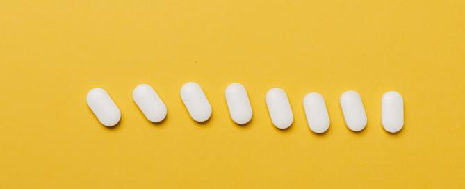vários comprimidos brancos enfileirados em fundo amarelo