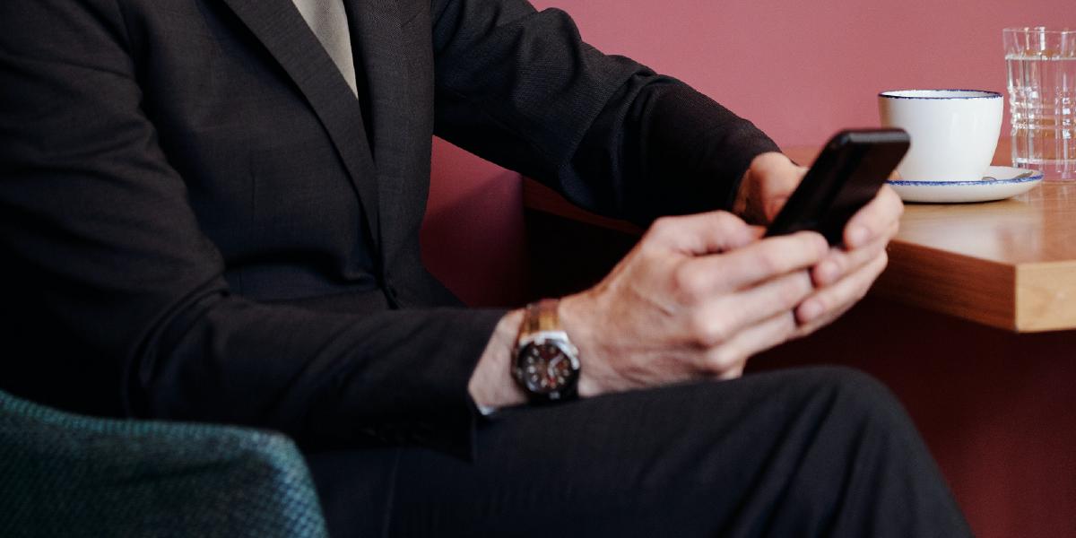 mãos de homem com um relógio no punho mexendo no celular