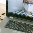 mulher de máscara e óculos na tela do computador