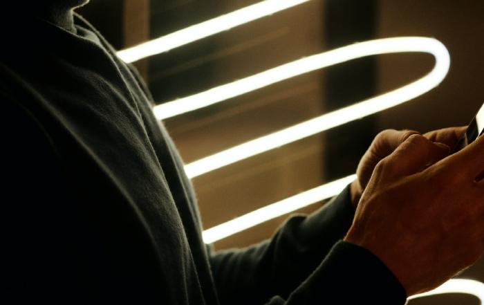 imagem escura de mãos segurando celular com luzes de led ao fundo