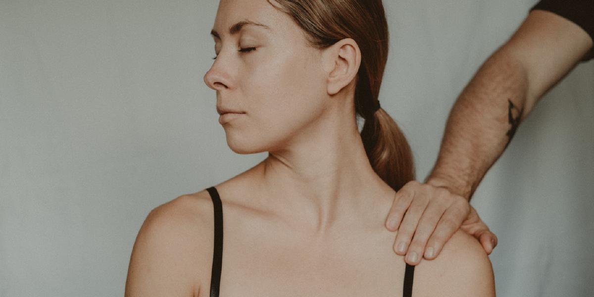 homem com a mão no ombro de mulher, que está com o rosto virado