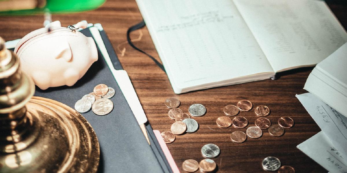 mesa com moedas jogadas, um caderno aberto com contas e um cofre em formato de porquinho