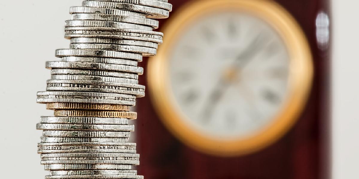 Pilha de moedas com relógio desfocado ao fundo