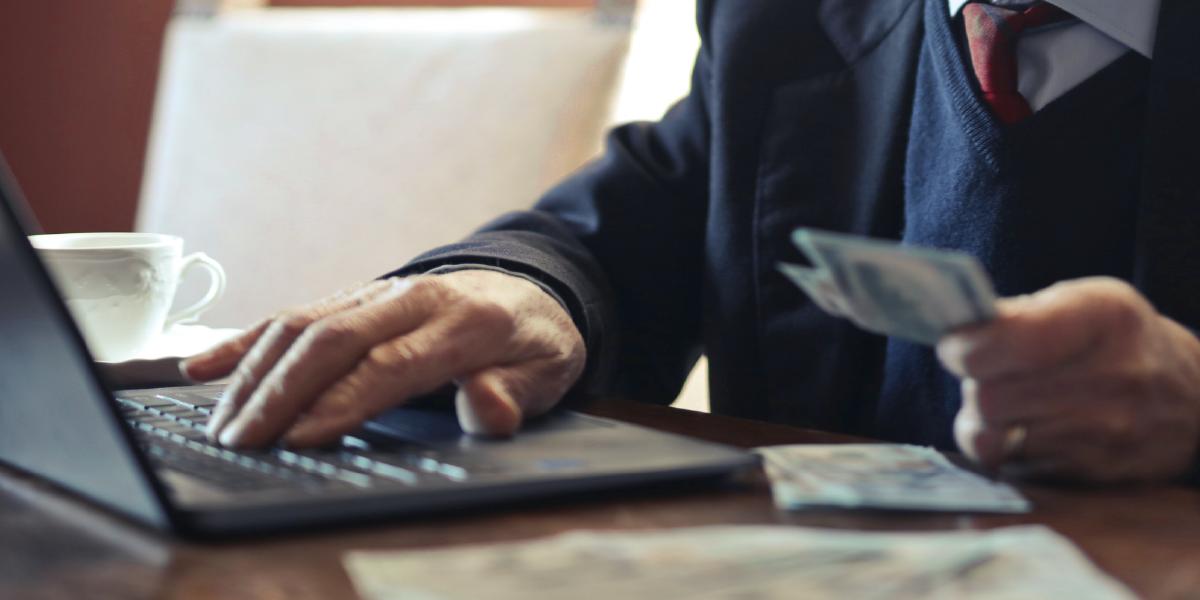mãos de idoso segurando dinheiro e mexendo em laptop