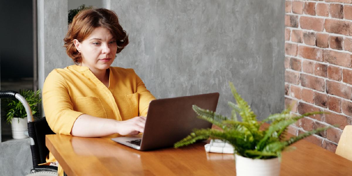 mulher cadeirante sentada mexendo em seu laptop