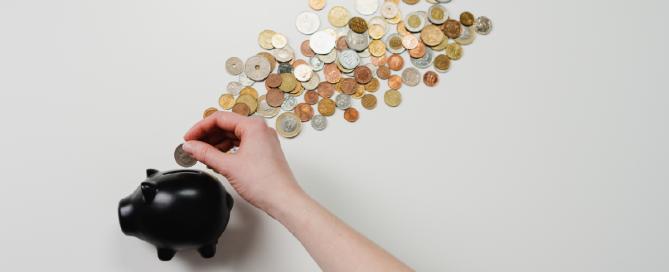 cofre preto de porquinho com moedas espalhadas