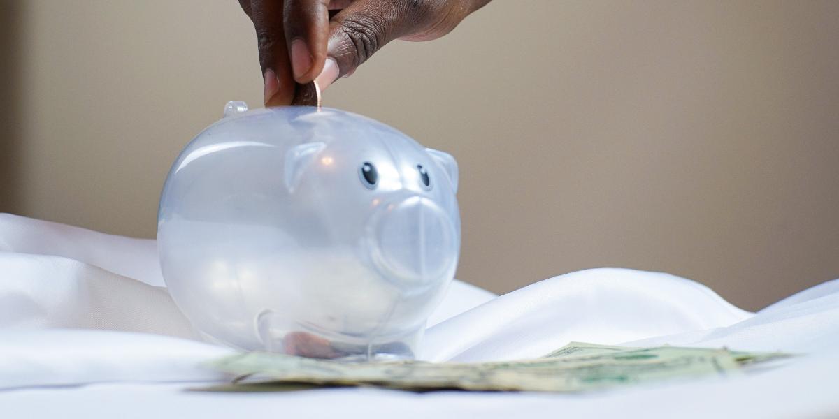 mão colocando uma moeda em cofre em formato de porquinho