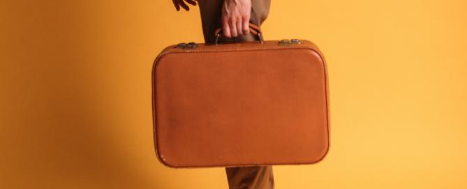 homem segurando bagagem de mão