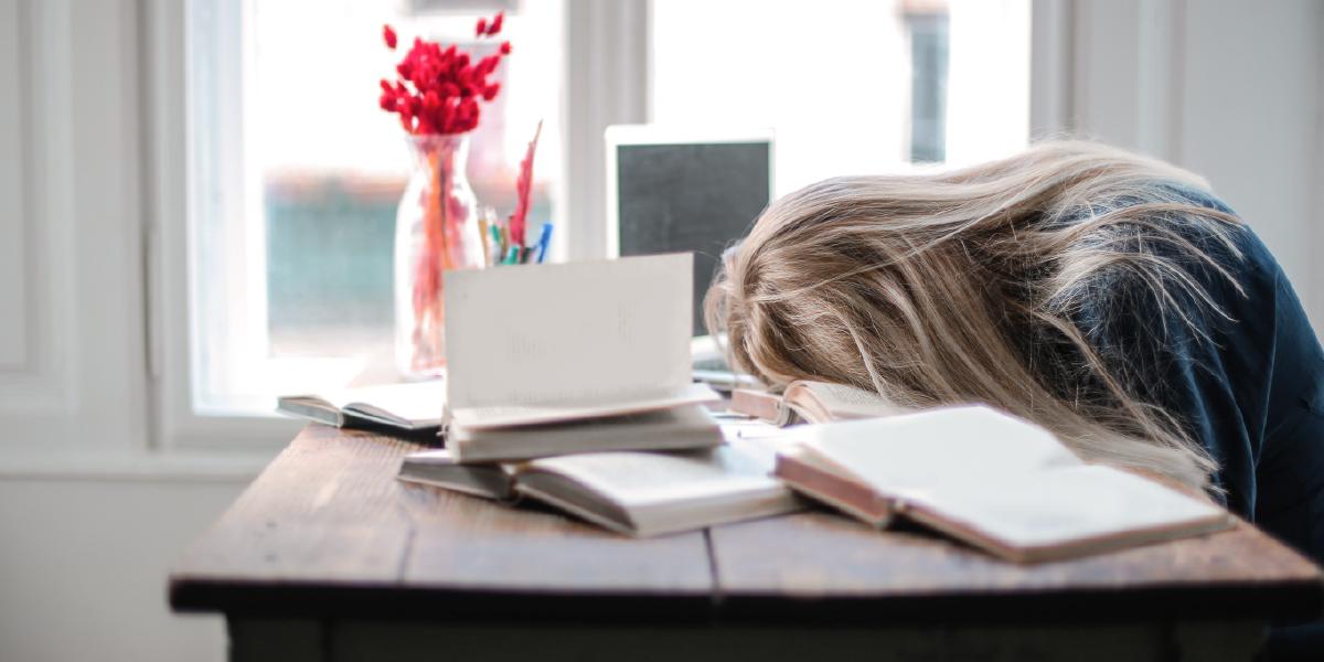 aluna loira sentada e com a cabeça deitada em cima dos livros na mesa