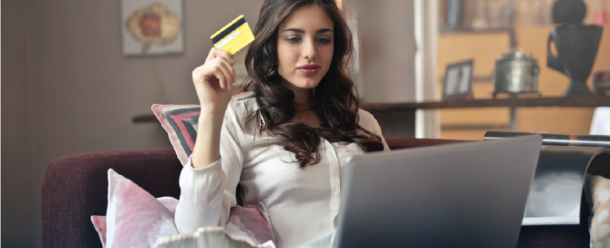 mulher em frente ao computador com sacolas de compras