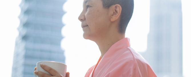 mulher careca asiática segurando xícara de chá