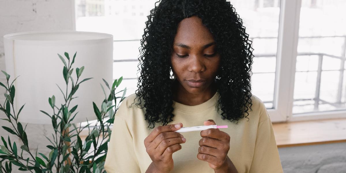 mulher olhando para teste de gravidez