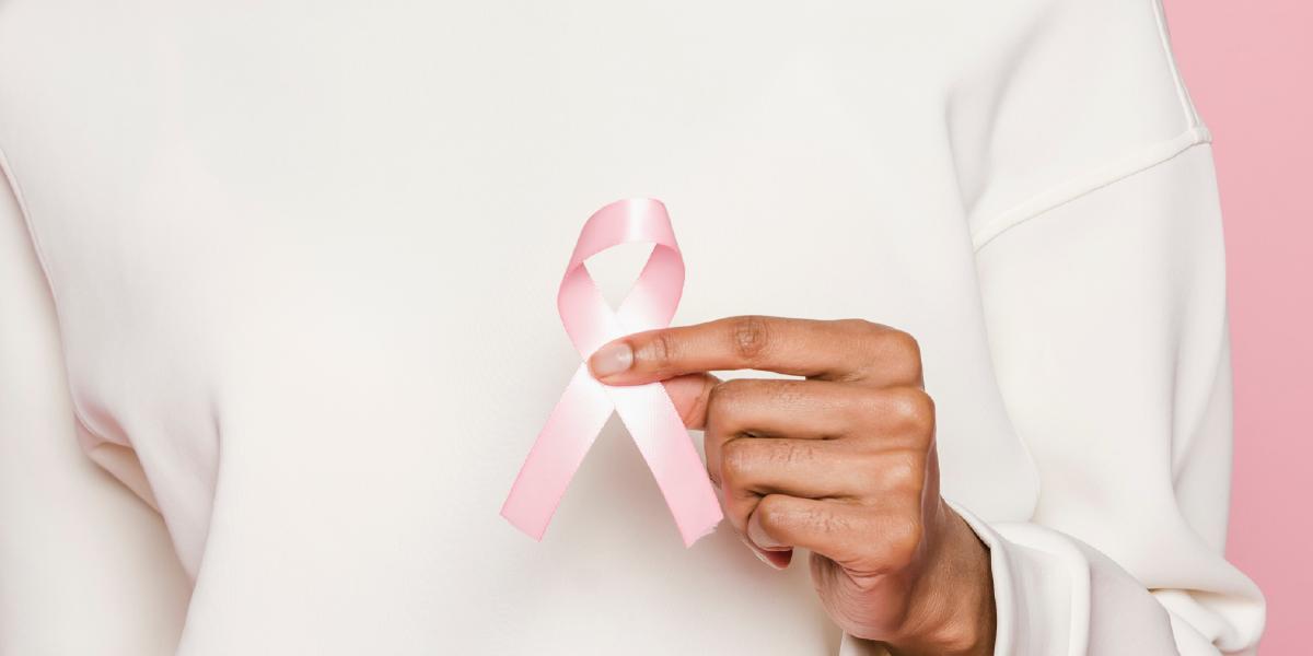 mão de mulher segurando laço rosa de outubro rosa